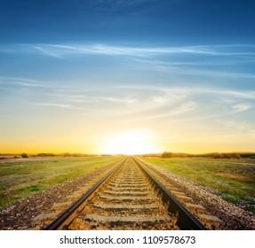 railroad among a green fields to a dramatic sunset