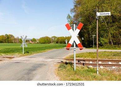 railroad crossing with Andreaskreuz in nature with blue sky