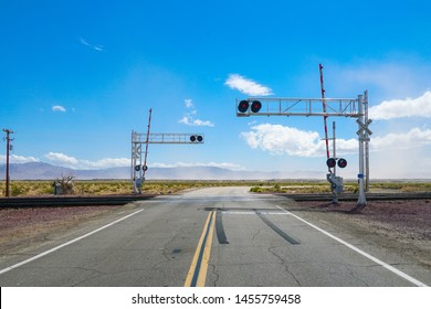 Railroad crossing gates on a road in the Mojave Desert in the Southwestern United States. California.