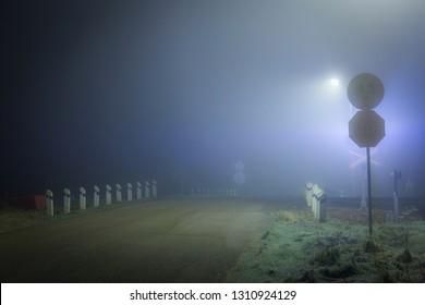 Railroad crossing at misty night.