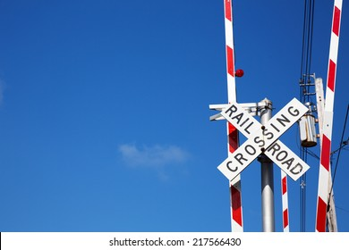 Railroad crossing sign against blue sky background, with space for your text.