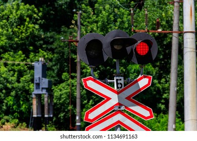 Railroad crossing sign with blinking red lights of semaphore