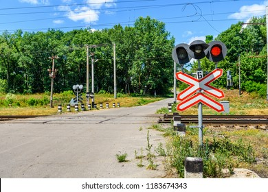 Railroad crossing sign and blinking semaphore in front of railroad crossing