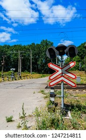 Railroad crossing sign and semaphore in front of railroad crossing