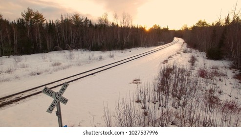 Railroad crossing sign with tracks and pink winter sunset