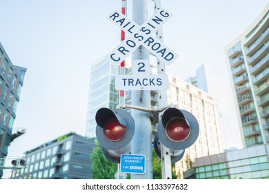 Railroad crossroad sign semaphore with buildings in the background.