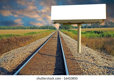 A railroad going thru a farm with a roadside billboard
