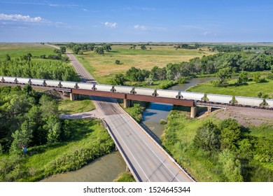 railroad, highway and river crossing in Nebraska Sandhills - aerial view with a freight train
