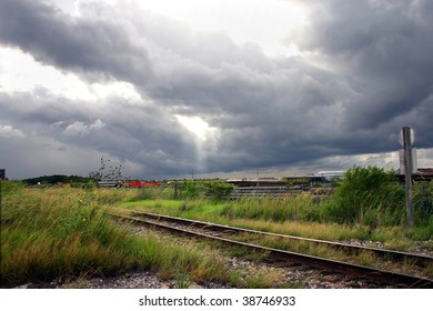 a railroad at an industrial part of town during a stormy day
