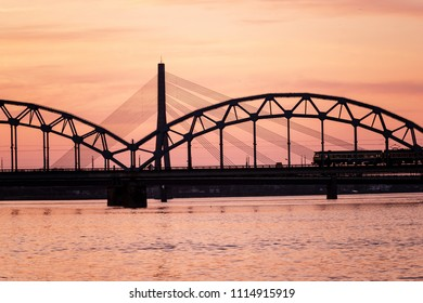 railroad metal bridge silhouette over river of Daugava in Riga, Latvia in dark red sunet with clouds. train leaving