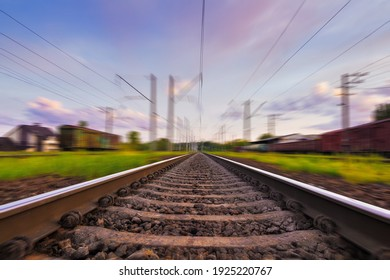 Railroad in motion with motion blur effect at sunset with beautiful sky and purple clouds. Railway transportation.