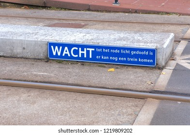 Railroad sign in the Netherlands with text Wait for the red light to go out before crossing the railroad tracks.