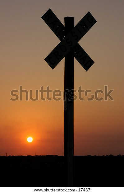 A railroad sign at sunset.