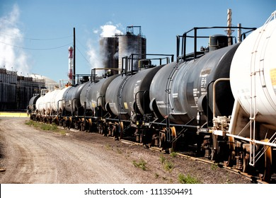 Railroad tank cars carrying liquid sulfer, parked on a rail siding at a fertilizer factory.