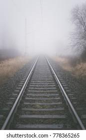 Railroad track into a fog in winter