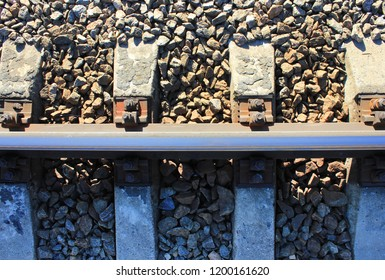 Railroad Track Top View of Concrete Sleepers, Ballast Bed of Gravel Crushed Stones and Metal Rail Close Up. Industrial Details of Train Railway Track, Vintage Old Rail Road Background
