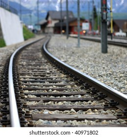 Railroad track with train station in the background