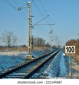 Railroad track in winter country with sign of speed hundred