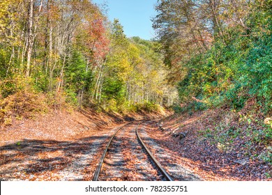 Railroad tracks in autumn fall in West Virginia with golden foliage, fallen leaves and road curve