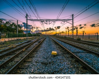 railroad tracks in the city during sunrise