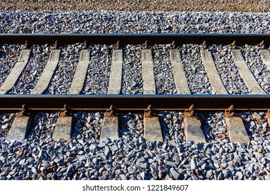 Railroad tracks with concrete sleepers. Detailed image of a railway track with gravel dumping. Side view.