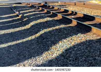 Railroad tracks in early morning light with shadows