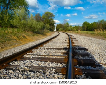 Railroad tracks going around a bend with a blue sky in southwest Virginia.