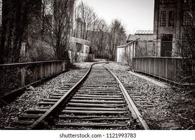 Railroad tracks going through an abandoned city with old buildings