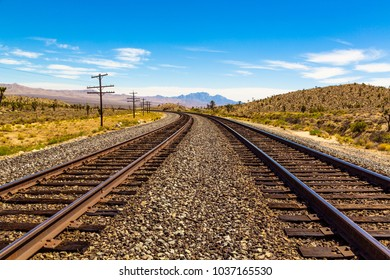Railroad tracks going through Mojave Desert in California with beautiful view