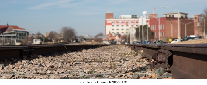 Railroad tracks from the ground level in an urban setting.