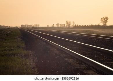 Railroad Tracks Receding into Golden Prairie Sunset