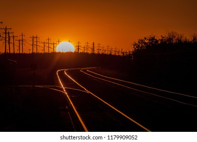 Railroad Tracks in Shadow Lit by Setting Sun
