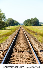 Railroad tracks stretching into the distance. Sunny summer day, blue sky.