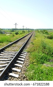 Railroad tracks that run off into the distance among green grass on summer sunny day