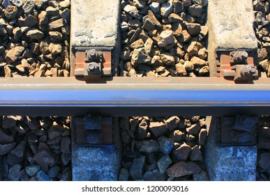 Railroad Tracks Top View. Concrete Sleepers, Ballast Bed of Gravel Crushed Stones and Metal Rail Close Up. Industrial Details of Train Railway Track, Vintage Old Rail Road Background