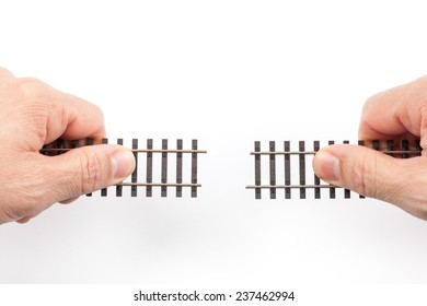 Railroad tracks toys in two hands ready for connecting isolated on white background