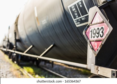 Railroad train of  black tanker cars transporting crude oil on the tracks. Hazardous material sign 1993 denoting flammable liquids.