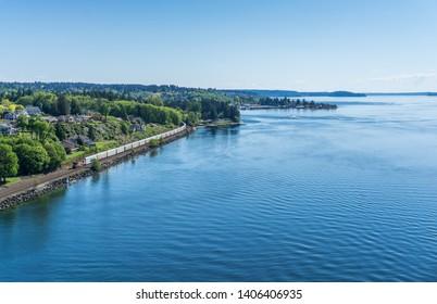 A railroad train moves along the shore of the Tacoma Narrows waterway.