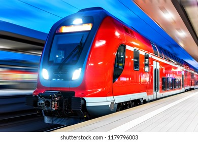 Railroad travel and railway transportation industrial concept: modern red high speed electric passenger commuter double deck train at the illuminated station platform at night with motion blur effect