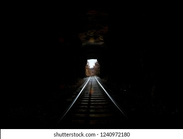 Railroad tunnel dark inside looking out into the daylight. Rail tracks running off into the distance through the tunnel opening. Fall leaves on branches. Light at the end of the tunnel concept