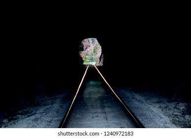Railroad tunnel dark inside looking out into the daylight. Rail tracks running off into the distance through the tunnel opening. Woods and trees. Light at the end of the tunnel concept