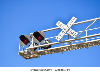 Railroad warning crossing sign under clear blue sky