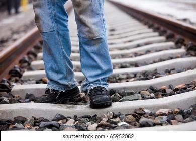 railroad worker in safety shoes is walking on the splints