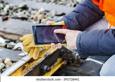 Railroad worker using tablet PC on railway