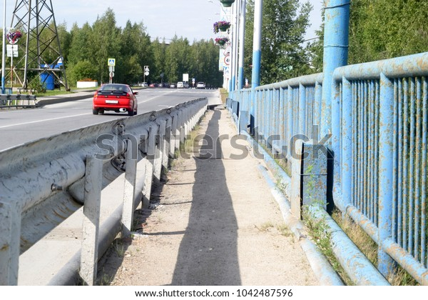 The rails of the road bridge cast a shadow, on the road, the summer and autumnal background