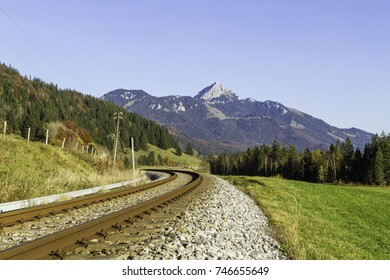 Railway along the fields of green grass in the mountains. Bavarian alps in the background, Wendelstein area, Germany.