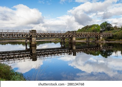 Railway beam bridge crossing River Lochy on stone piers beside Old Inverlochy Castle in Fort William, Highland, Scotland, UK. The cloud scape and blue sky reflects like a mirror on the quiet waters.