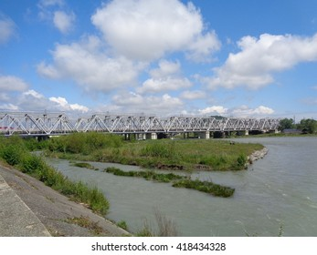 Railway bridge across the river, green islands, blue sky with clouds