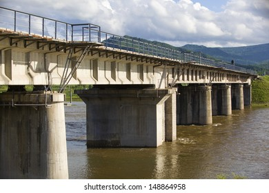 The railway bridge across the river in summer