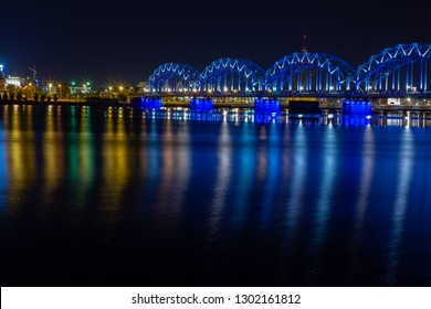 Railway Bridge crosses the Daugava river in Riga at night. Panoramic view on Riga the capital of Latvia city from left bank of Daugava river.